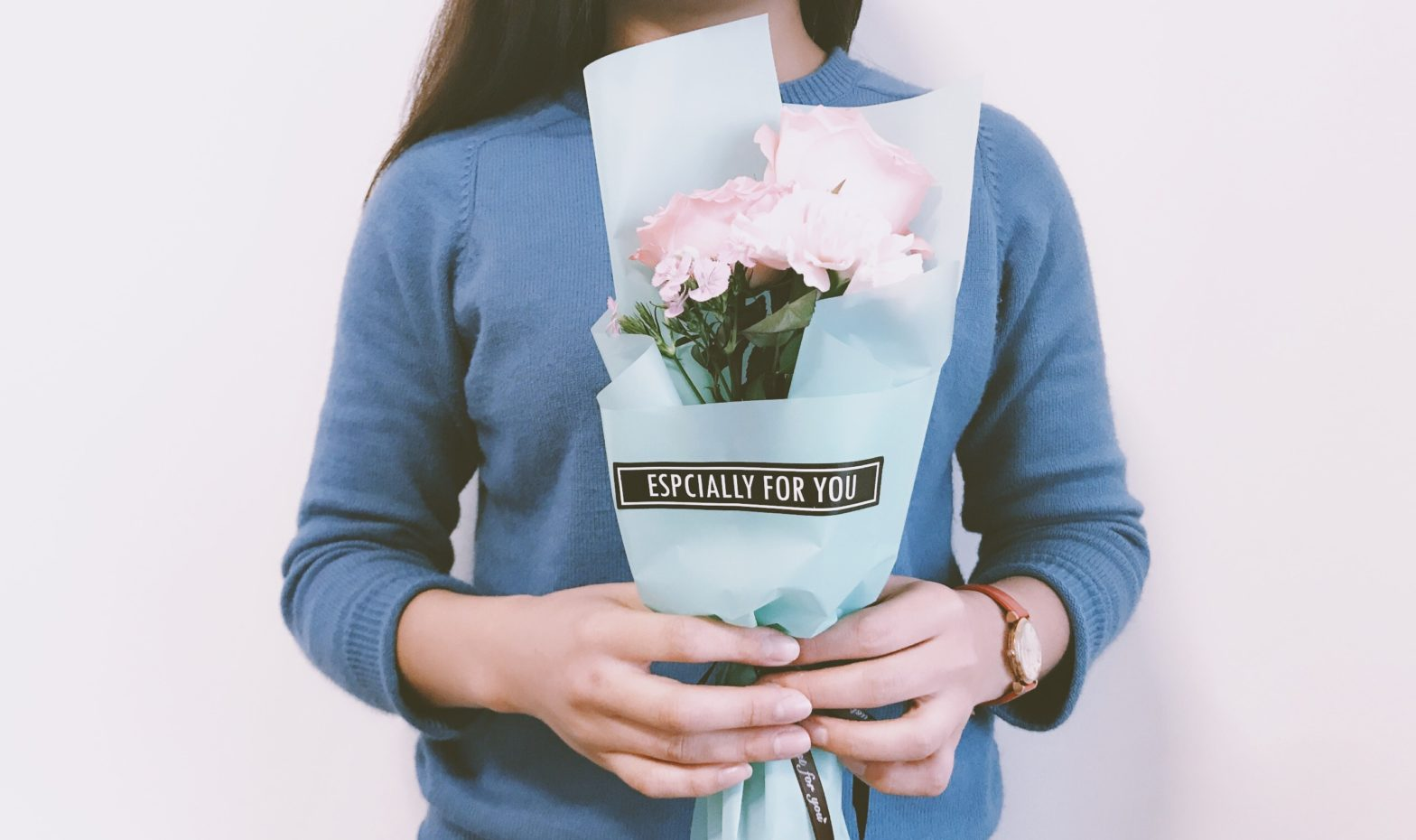Woman receiving flowers that say especially for you.