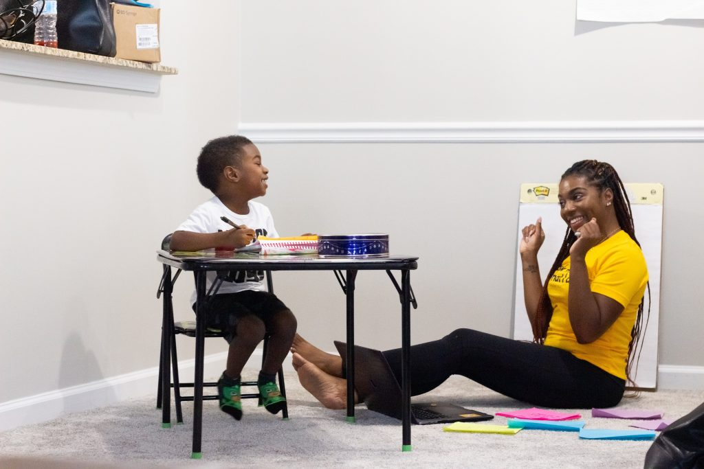 Mother teaching young child school skills.